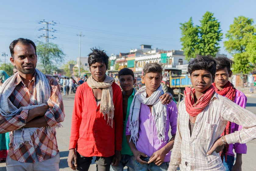 Young men wait for contractors at the labour naka in Udaipur. At least one male from most of the families in the district migrates for work (file photos)