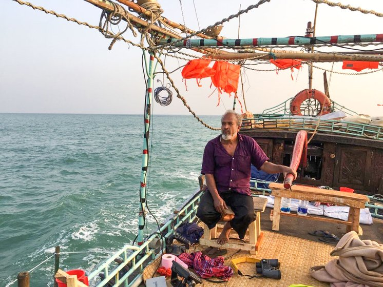 An owner-captain of a modified fishing boat, Sobahan Shordaar guides his boat FB Manikjaan through the waters of coastal Bangladesh