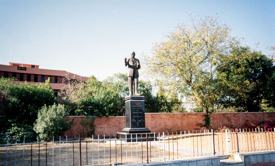 An Ambedkar statue stands at the street corner facing the traffic