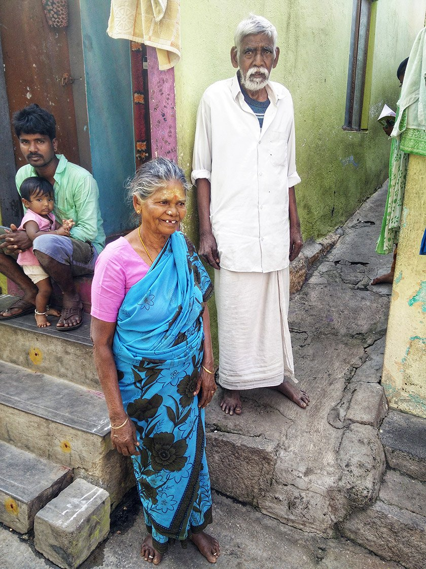 An elderly man and woman standing outside houses