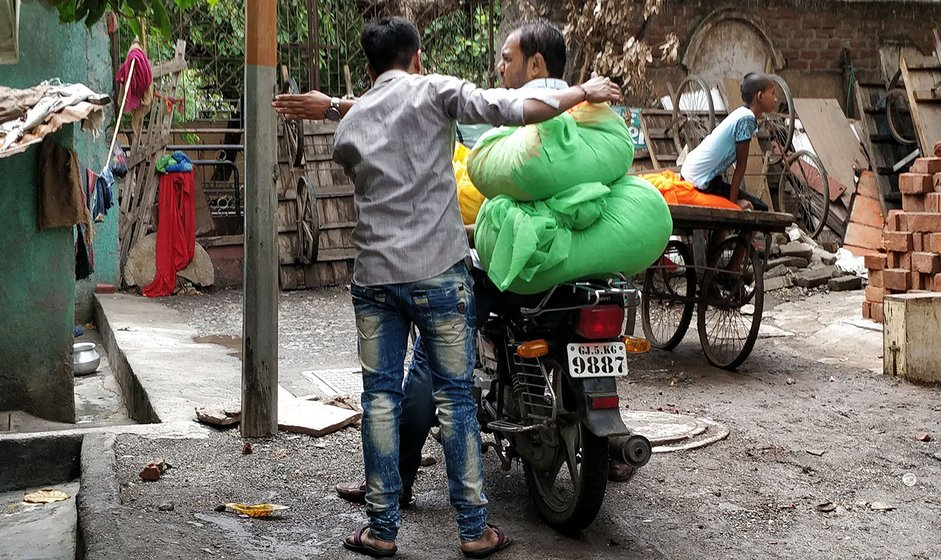 Men getting bundles of saris to the ladies who work on them