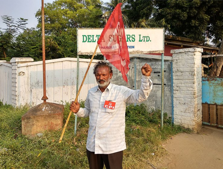 Man holding flag outside the gate of the Delta Sugars factory. he is protesting the closure of the company.