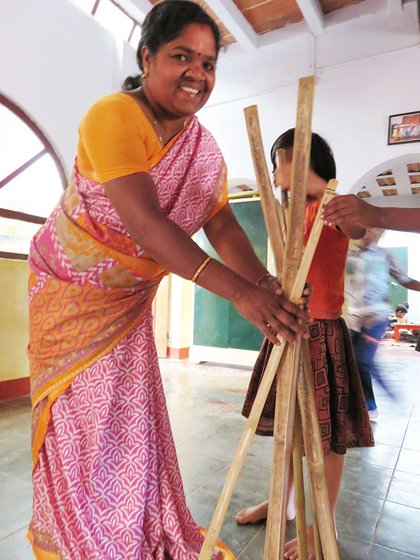 Shanthi Kunjan holding sticks that the children will use to measure their homes