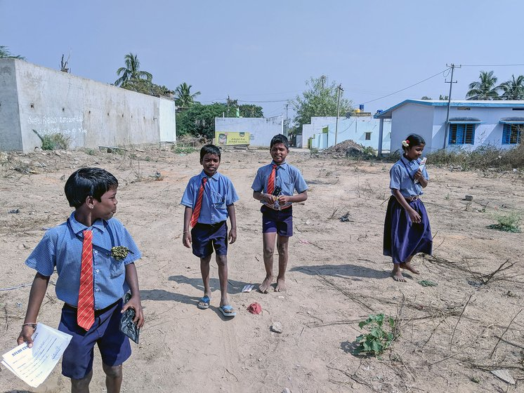Three young boys and a young girl in their school uniforms walking through an open area