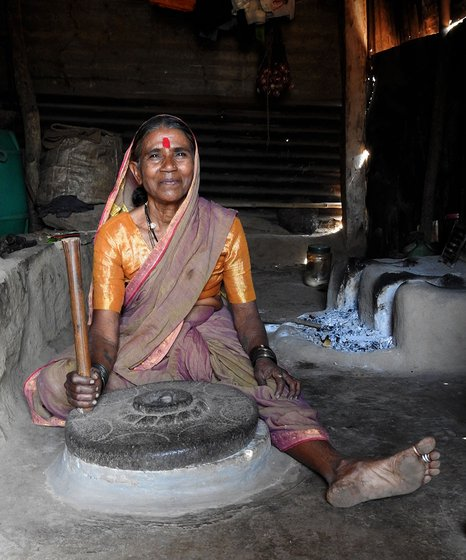 Woman sitting on the floor of a house with a grindmill