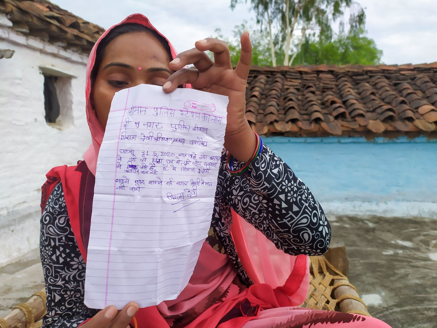 Girija with the letter of complaint for the police that she had her 14-year-old daughter Anuradha write on her behalf