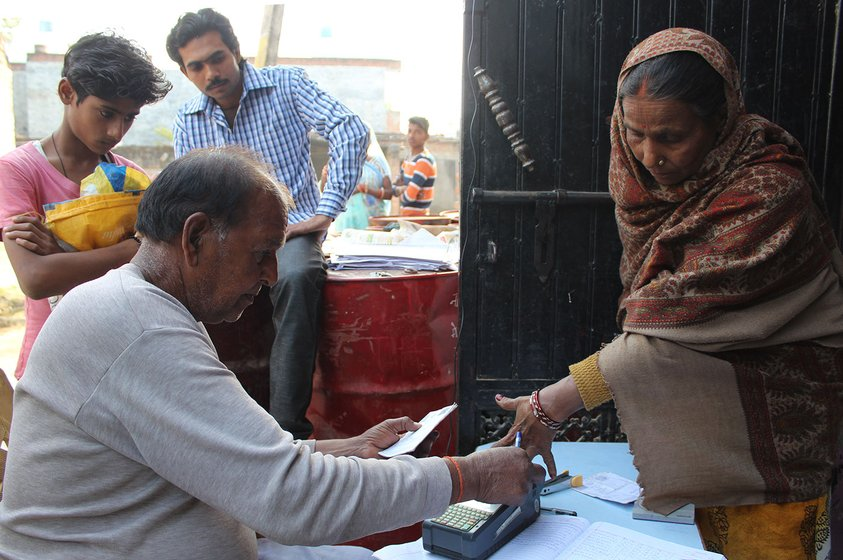 A man taking fingerprints on a machine for Aadhaar verification