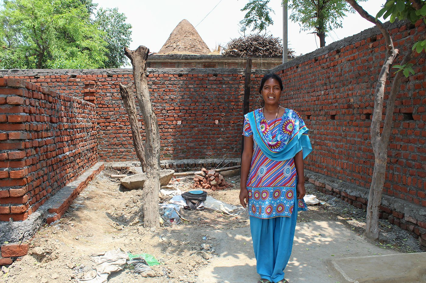 Mangola Singh in front of a semi constructed room which she has been trying to build for herself in the courtyard of her home in the village of Nandpur (Udham Singh Nagar), Uttarakhand