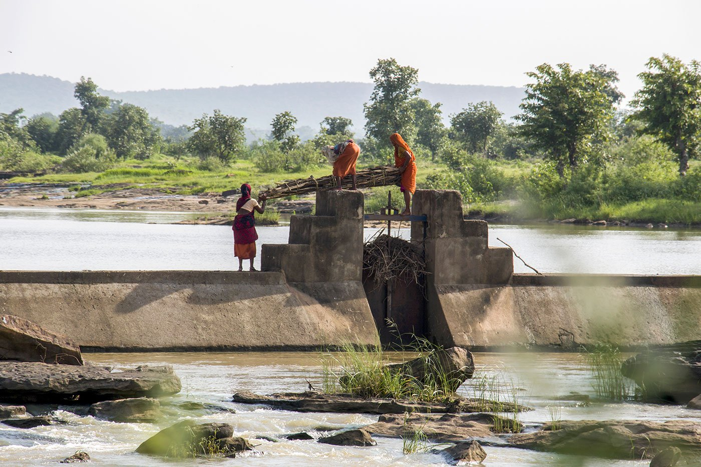 Women crossing the sluice gate of a dam, carrying their daily load of firewood