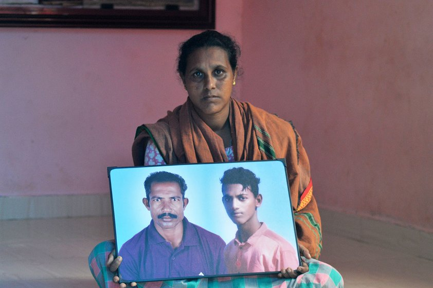 Woman sitting on the floor holding a framed photograph of her husband and son