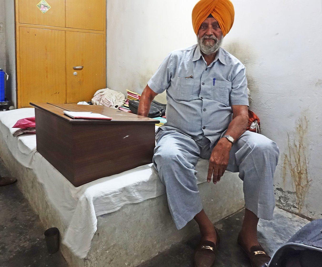 A man sitting on a bed in an orange turban