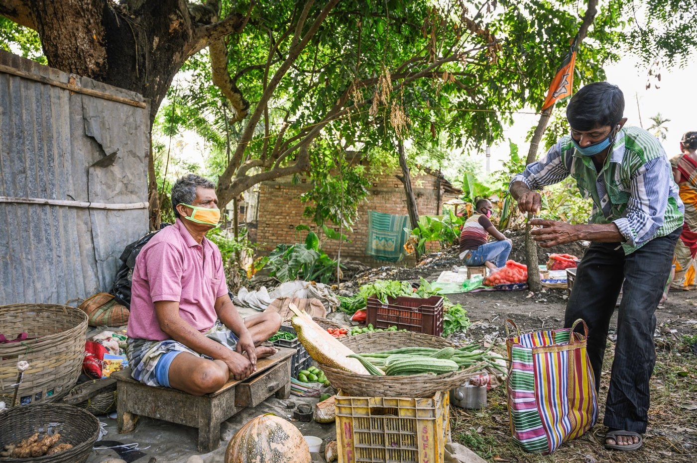 "Ram Dutta, a 56-year-old vegetable seller, buying lemon tea from Santi Halder. His income has dropped to half his daily earnings of Rs. 300. He says, ""I didn't have a lot of sales before, now it's even worse."" Santi Halder, 48, has been selling jhal muri (a popular street food in West Bengal) for 20 years, but with lockdown restrictions on cooked food, is selling tea. His income too has dropped from Rs. 250-300 to Rs. 100-120 a day."