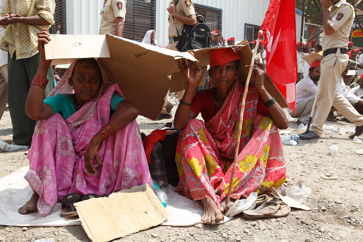 Two women sitting at Azad maidanIn Mumbai, covering their heads with cardboard boxes in the blistering heat.
