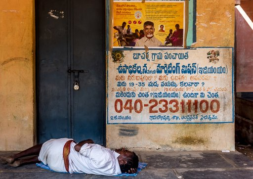 03-unemployed-sc-man-rests-at-ration-shop-and-unemployment-helpline-number-of-egmm-scheme-on-the-wall-Bucharla-0572-RM-Staying half-hungry due to the demonetisation 'drought'.jpg