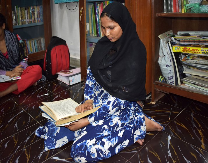 Bashira Shah reading a book at the library