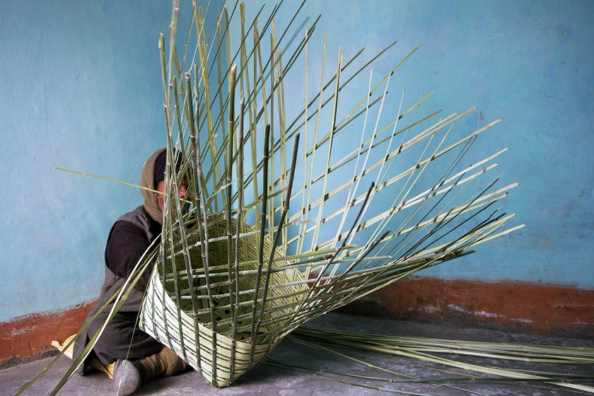 A man is sitting on the floor inside his house and weaving bamboo strips into a basket