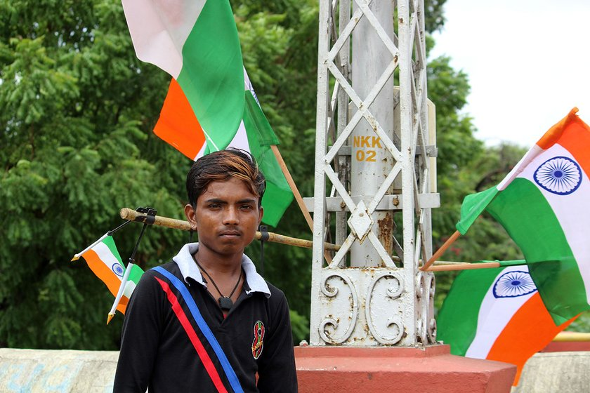 Mahendra standing in front of a pole that has Independence Day flags attached to it
