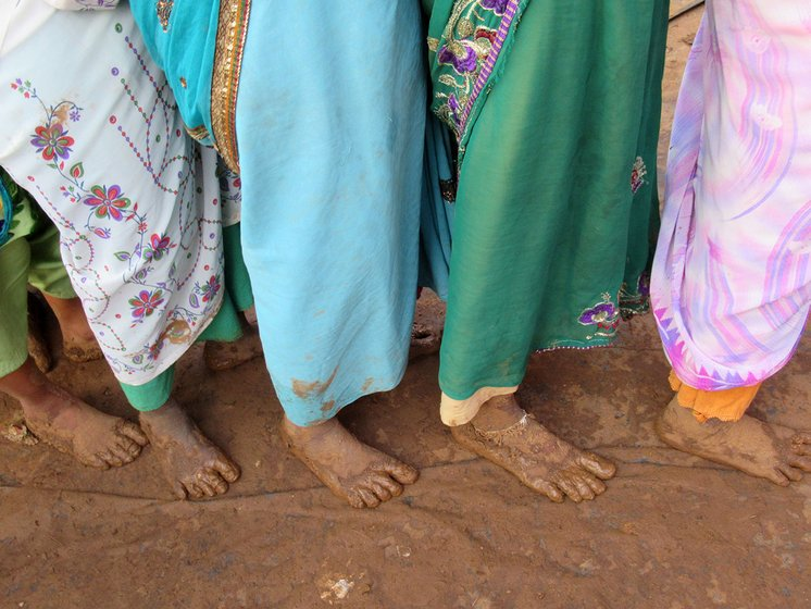 A group of women standing with bare feet on a muddy ground