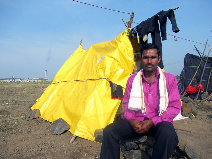 A man sitting next to a makeshift hut made of yellow tarpaulin