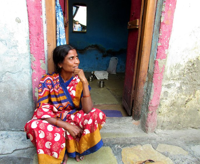 Kavita Kamble sitting outside the doorway of her house