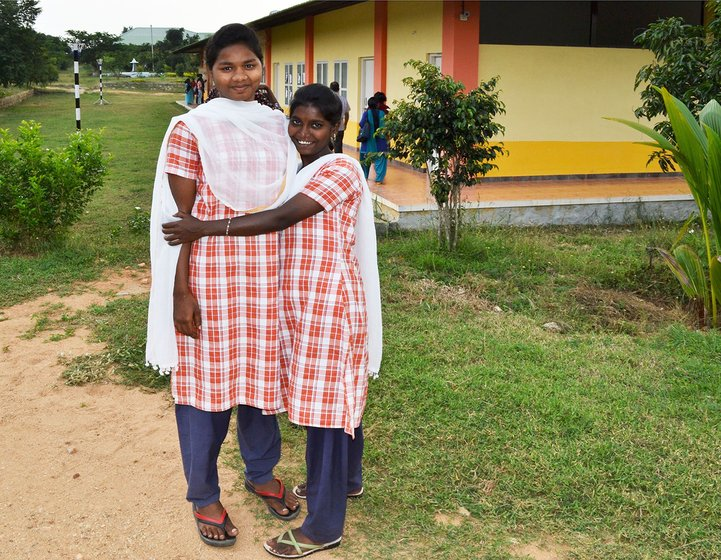 Two girls hugging in front of a school