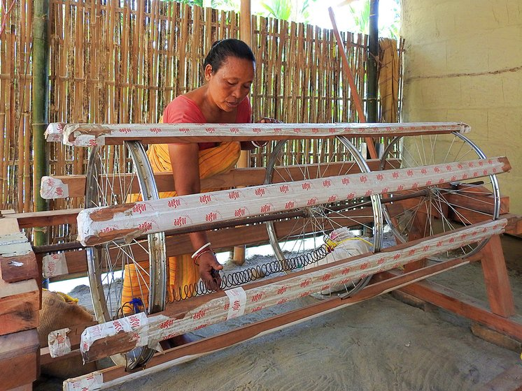 Sama tinkering with the warping drum that has recently been installed at her home. The warping drum is used to prepare the vertical yarn known as 'warp', which is later loaded on the loom