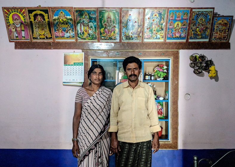 A couple standing in their home with images of various gods framed above them