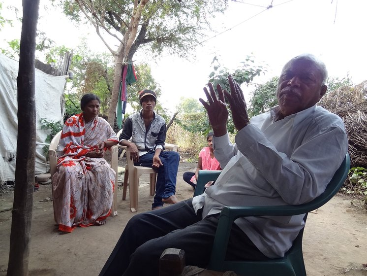 A man talking in the foreground with a man and woman sitting in the background in the village of Chikhli-Kanhoba