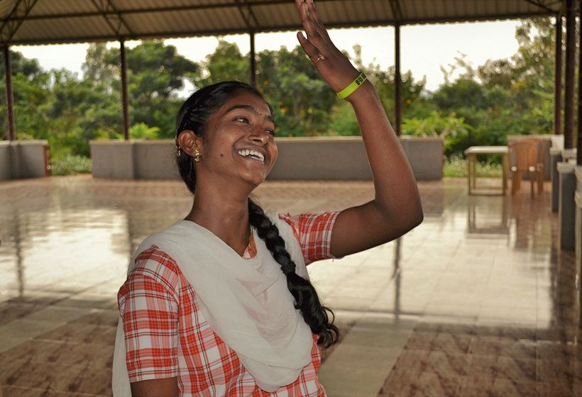 A girl laughing with one hand raised