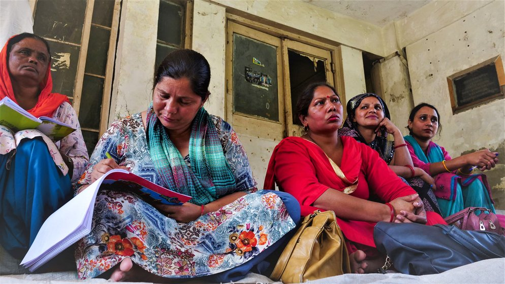 'We don't even have time to sit on a hartal,' says Sunita Rani; at meetings, she notes down (right) the problems faced by co-workers