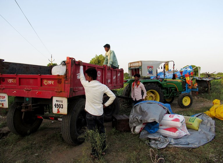 People loading gunny bags of bajra and utensils onto tractors