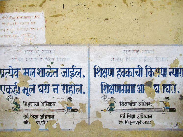 "Torn posters on a yellow wall school wall in Marathi at Hatkarwadi village in Beed district of Maharashtra. It says, ""Every kid will go to school, nobody will be at home""."