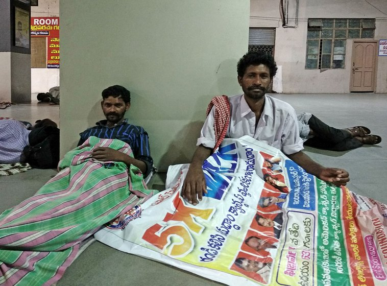 Kota Veera Vasantha Rao and Kotamarthi Yesu get ready sleep on a vinyl banner in Pandit Nehru Bus Stand in Vijayawada