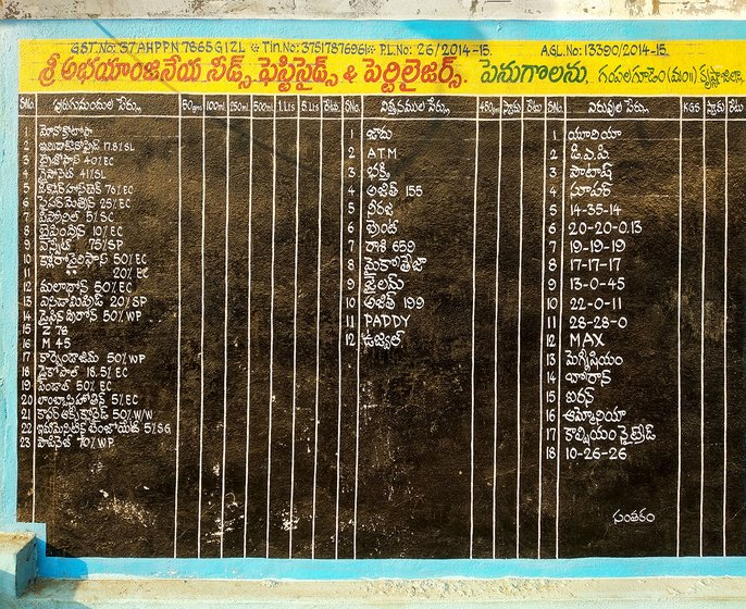 List of seeds, fertilizers and pesticides available in Abhayanjaneya Nursery, written on a wall.