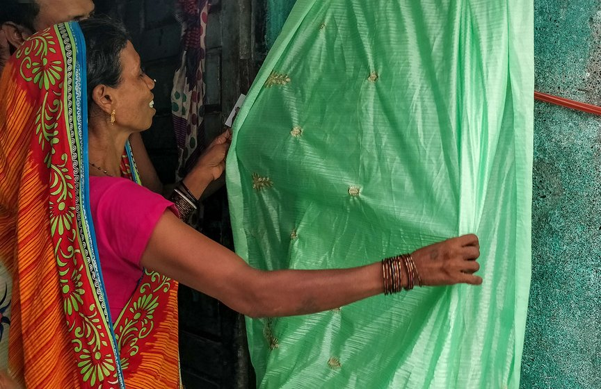 Shanti Sahu and her daughter Asha have fixed a rope outside their one room home in Mina Nagar to begin work on the saris that have been sent for the day. Shanti's husband, Arijit, looks on.