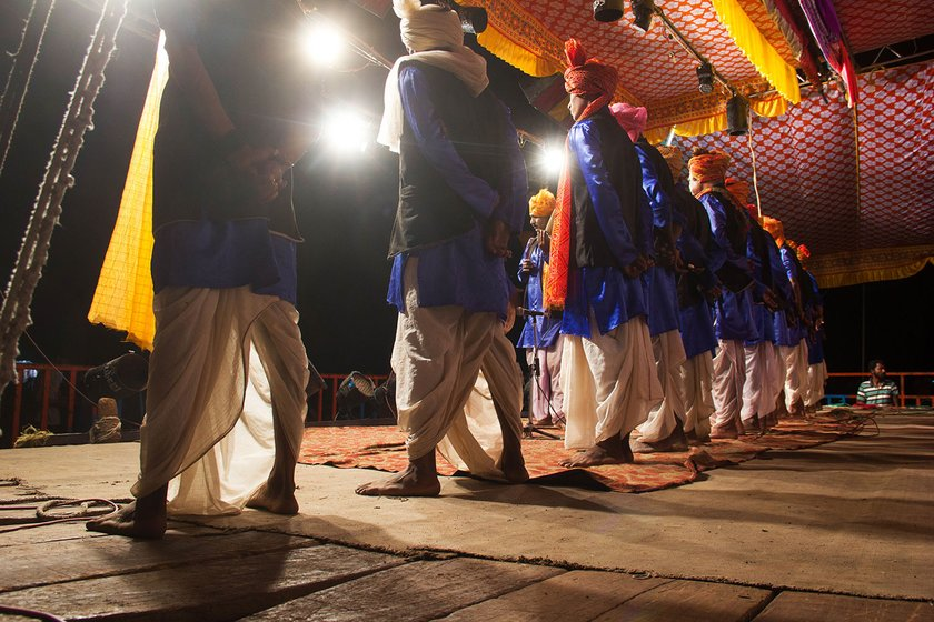 Male artists take position for the gan during the performance in Gogolwadi village, Pune district