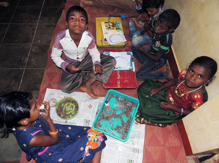 Adivasi children making bead chains in craft class
