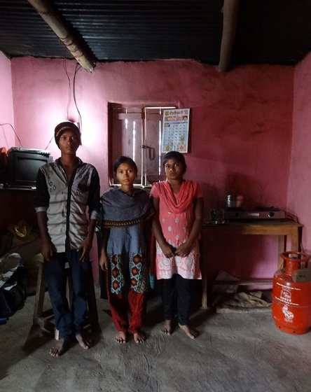 A young boy and two young girls, all sblings, stand in their house