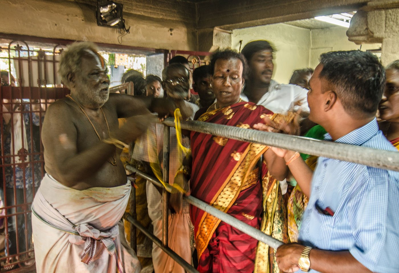 One of the priests at the Koothandavar temple begins the wedding rituals. He ties a yellow thread called thali around the neck of each aravani to consecrate her union with Aravan.