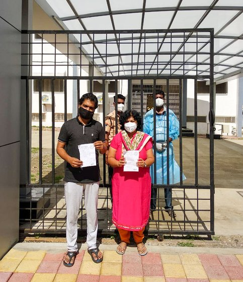 Tanuj and Shilpa with their discharge papers, outside the quarantine centre