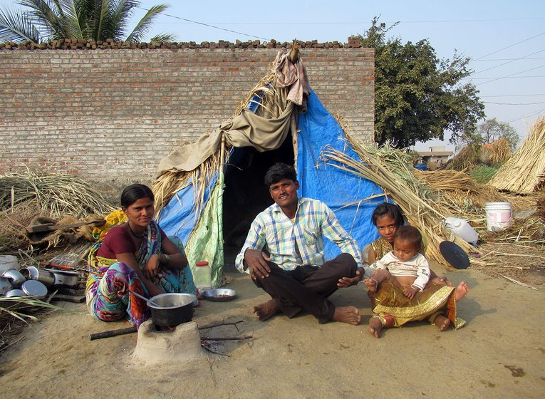 A man, woman and two children sitting outside a makeshift tent