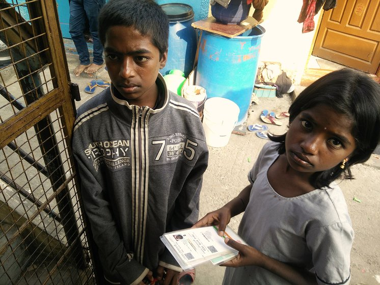 A young boy and girl holding their Aadhaar cards