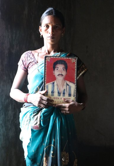 Tulshi holding a photo frame with her deceased husband's photograph