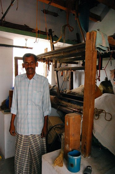 Vinayakam stands next to his disused loom.