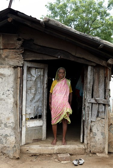 Left: A board announcing the resettlement of Sarubai's village Wadavali, which was submerged when the Warasgaon dam was built in`1994. Right: A few weeks ago, Sarubai's son asked her to leave his house; she now lives in this dilapidated hut at the entrance to the village