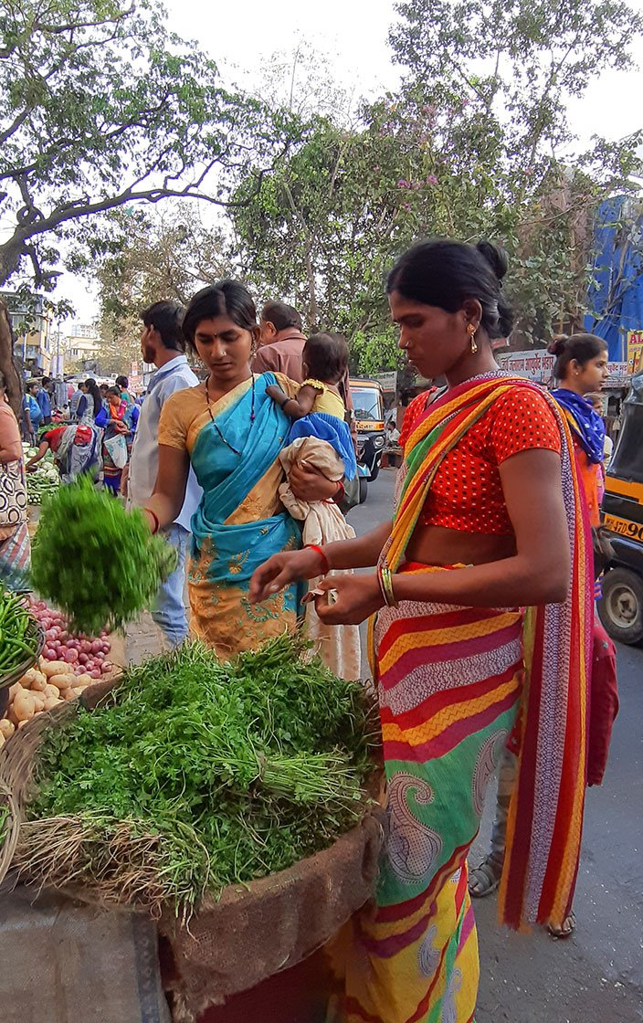 Pooja and Maya buying vegetables at the market.