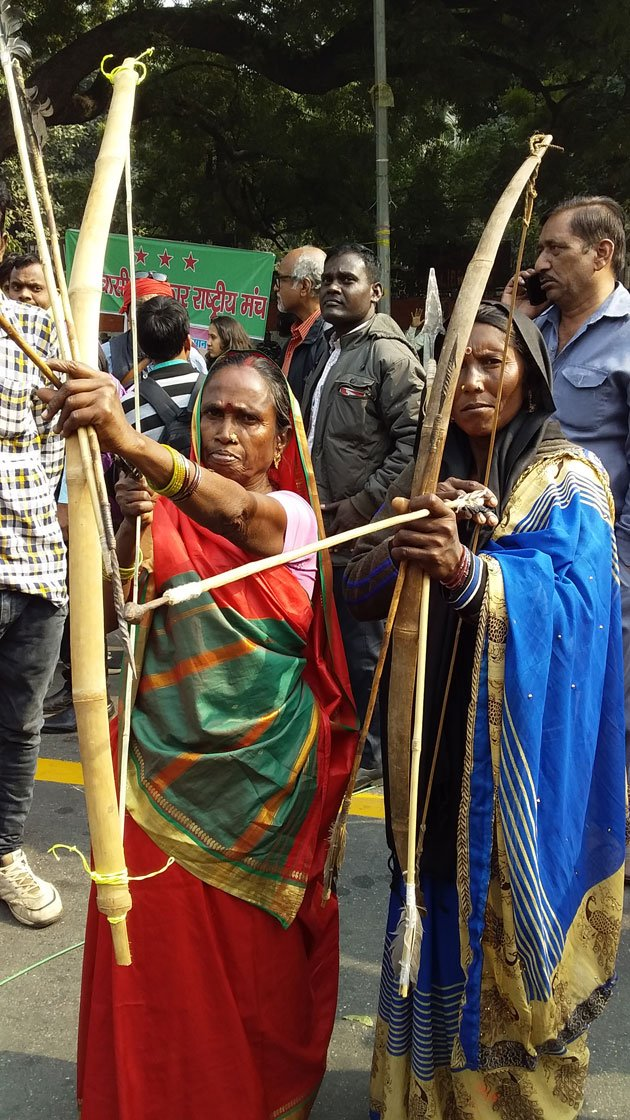 Rajkumari Bhuiya (left) of Dhuma village in UP's Sonbhadra district with the traditional bow and arrows her Bhuiya community used to defend their land. She is a member of the All India Union of Forest Working People and a leader in organising her community to file claims to forest resources.