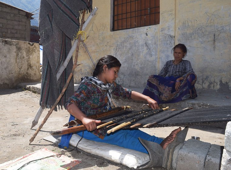 Woman weaving carpet outside her home.
