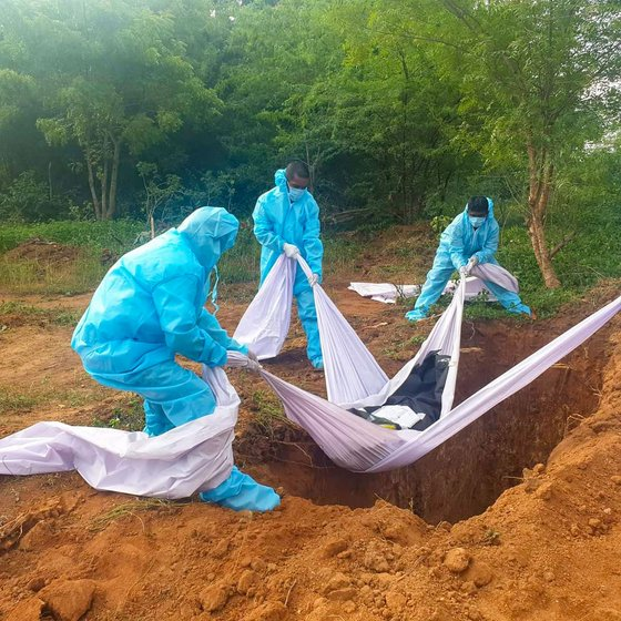 The volunteers lower a body into a pit eight feet deep, cover up the pit and pour a disinfectant powder across the grave