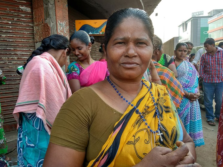 A woman standing at a street corner in Vijaywada